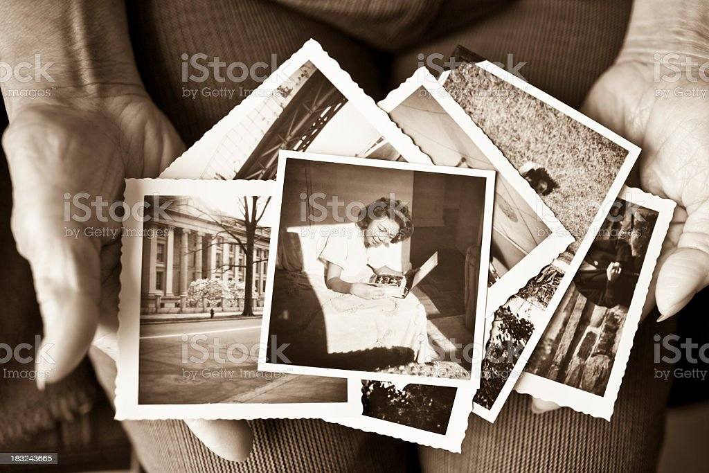 Elderly woman holding a collection of old photographs stock photo