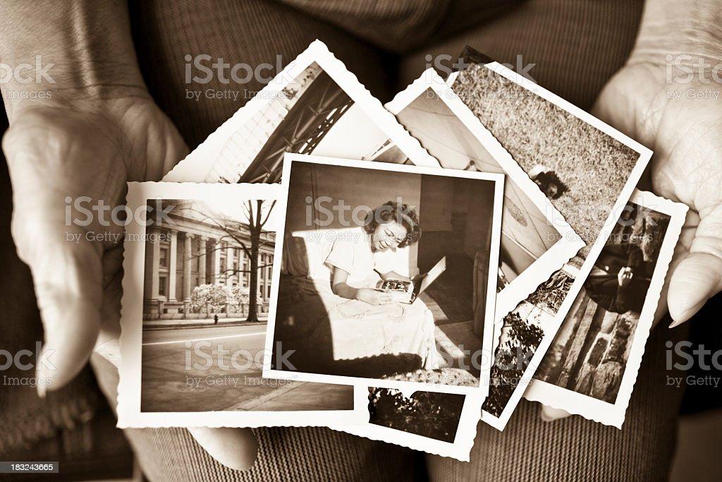 Ältere Frau hält eine Sammlung von alten Fotos – Foto