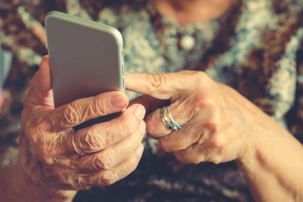 femme âgée tenant un téléphone portable - une seule femme senior photos et images de collection