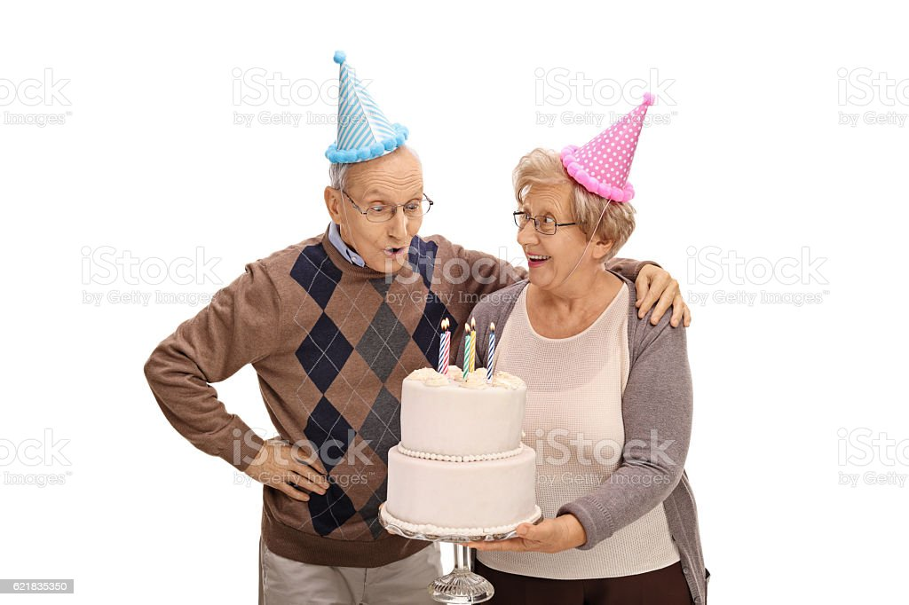 Elderly Woman Holding Birthday Cake And An Elderly Man Blowing Stock