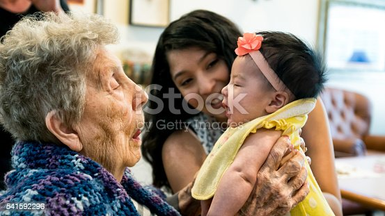 Beautiful, poignant image of a very old great grandmother holding her beautiful mixed race infant great granddaughter for the very first time as the baby's mother looks on with a big warm smile.  All three people have authentic facial expressions.
