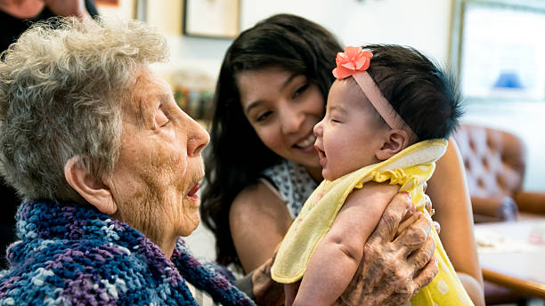 Elderly Woman Holding Infant Granddaughter as Mother Looks On Smiling stock photo