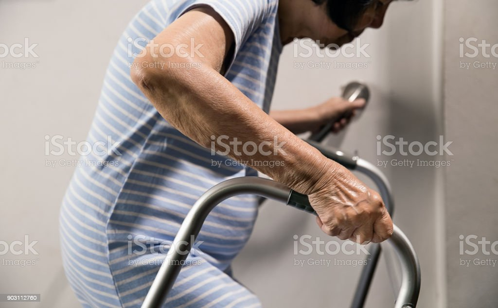 Elderly woman holding on handrail and walker for safety walk steps royalty-free stock photo