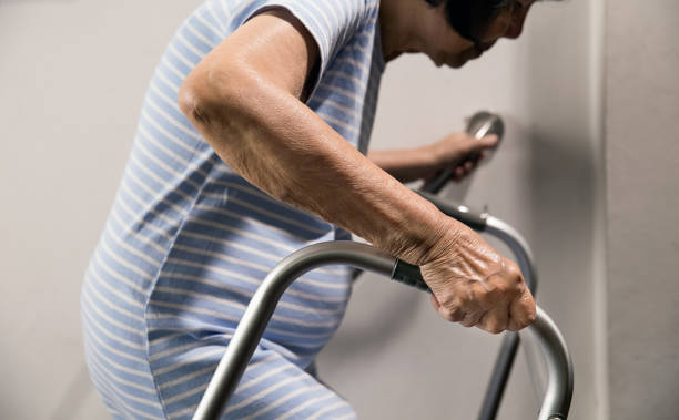 Elderly woman holding on handrail and walker for safety walk steps stock photo