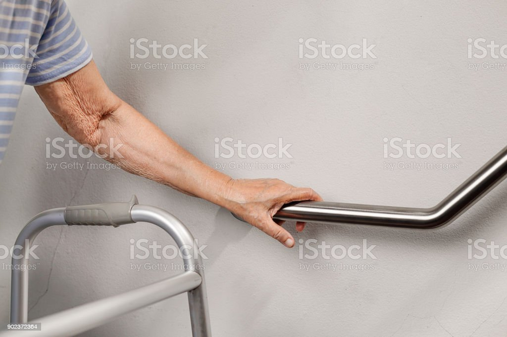 Elderly woman holding on handrail for safety walk steps stock photo