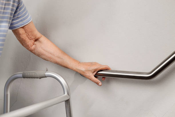 elderly woman holding on handrail for safety walk steps - gripping stock photos and pictures