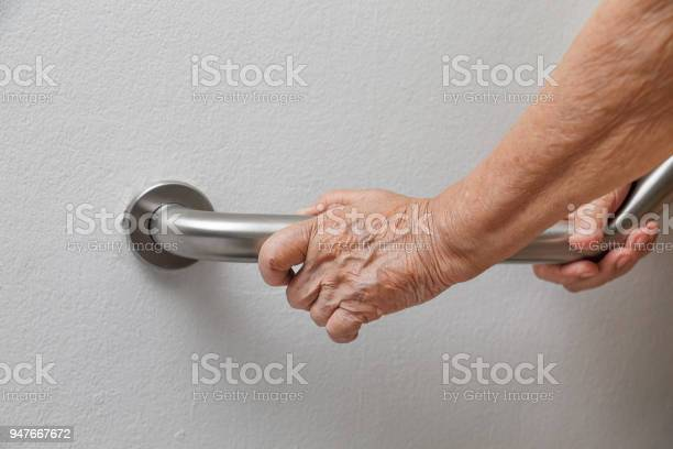Elderly woman holding on handrail for safety walk steps picture id947667672?b=1&k=6&m=947667672&s=612x612&h=fanbnz8gxq8aodlzguvdm1skxgyjqunw4ewreviaz c=