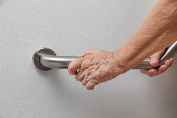 elderly woman holding on handrail for safety walk steps - afferrare foto e immagini stock