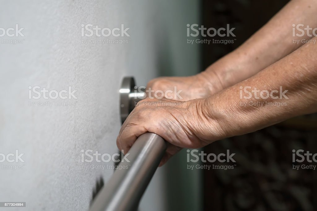Elderly woman holding on handrail for support walking stock photo