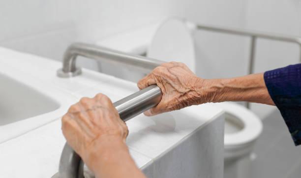 Ältere Frau hält auf Handlauf im Badezimmer – Foto