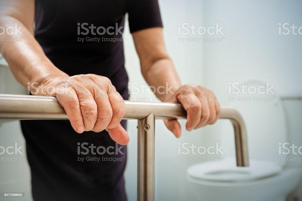 Ältere Frau hält am Handlauf im Badezimmer. – Foto