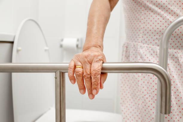 Elderly woman holding on handrail in toilet. stock photo