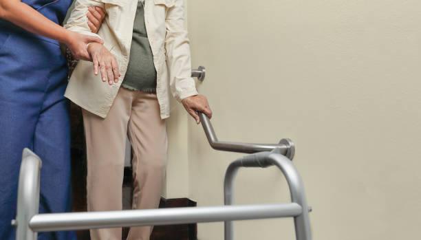 Ältere Frau hält sich mit Pfleger auf dem Geländer – Foto