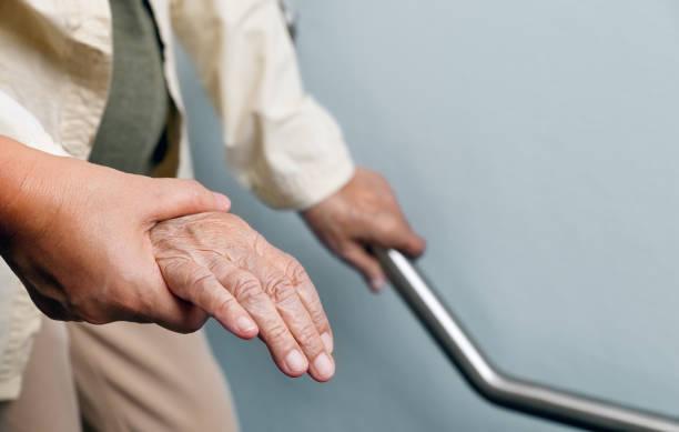 Ältere Frau hält auf Handlauf mit Betreuer – Foto