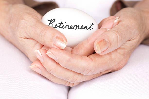 Elderly woman holding retirement egg stock photo