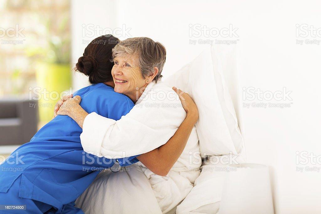 elderly woman hugging caregiver on bed stock photo