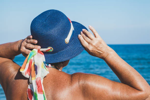 Elderly woman in a beach hat looking at the sea Elderly woman in a beach hat looking at the sea summer sunny day irradiation stock pictures, royalty-free photos & images