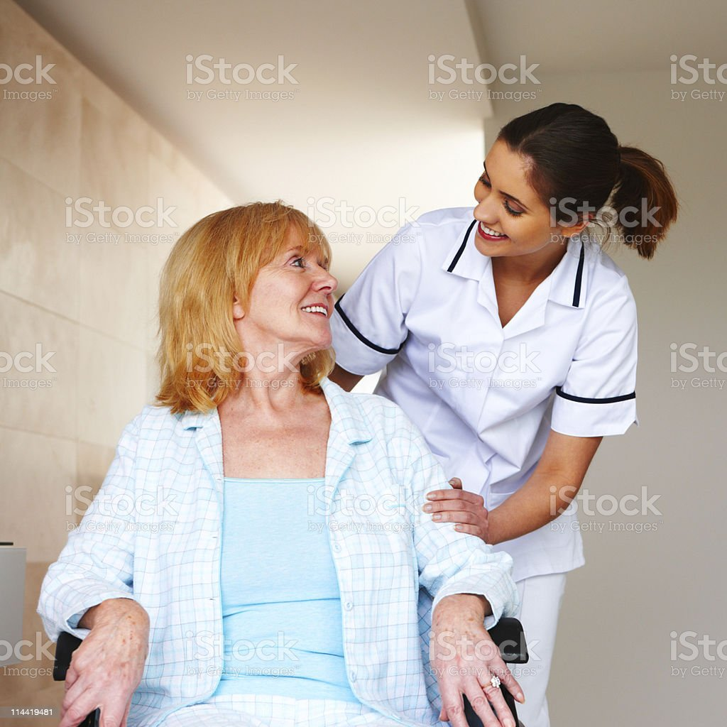 Elderly Woman in a Wheelchair and Her Nurse royalty-free stock photo