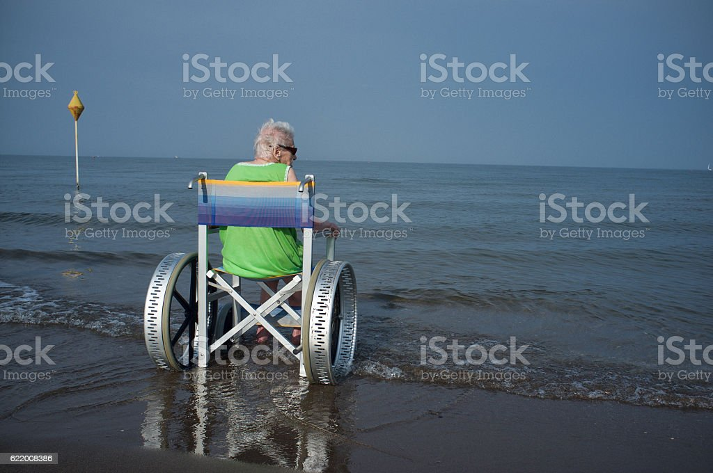 elderly woman in a wheelchair in the sea stock photo