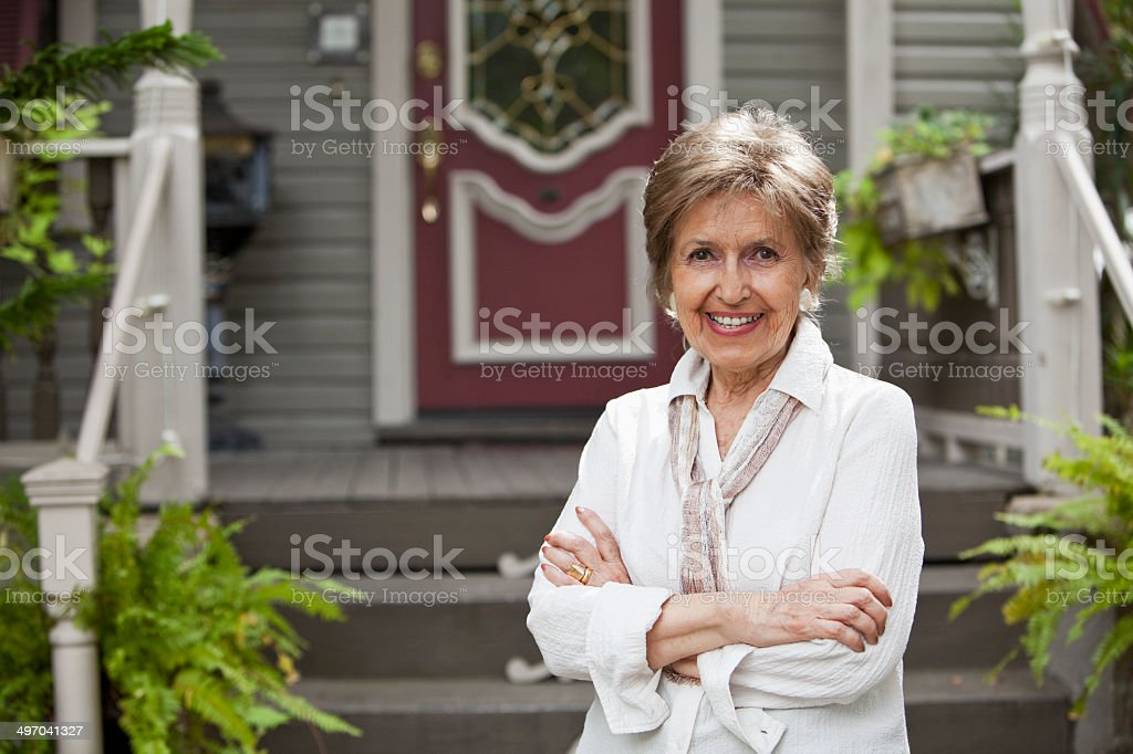 Elderly woman in front of home stock photo