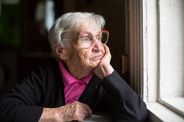 Elderly woman in glasses thoughtfully looking out the window. stock photo
