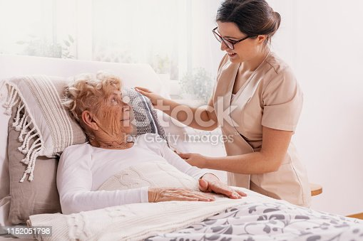 istock Elderly woman in hospital bed with social worker helping her 1152051798