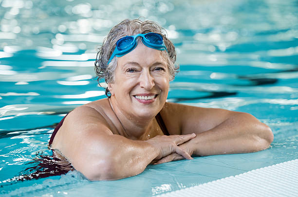 anciana en la piscina - natación fotografías e imágenes de stock