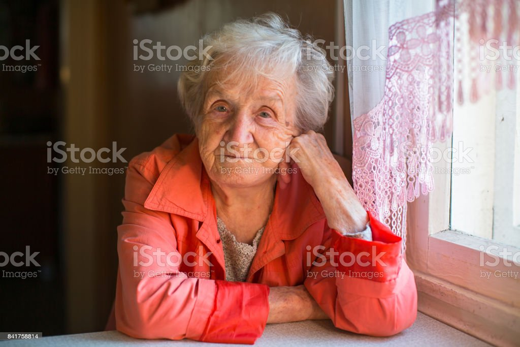Elderly woman in red jacket sitting at the table in the house. stock photo