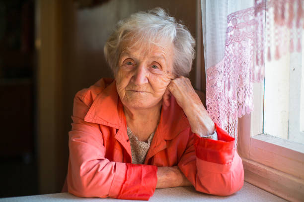 elderly woman in red jacket sitting at the table in the house. - senior housing stock photos and pictures