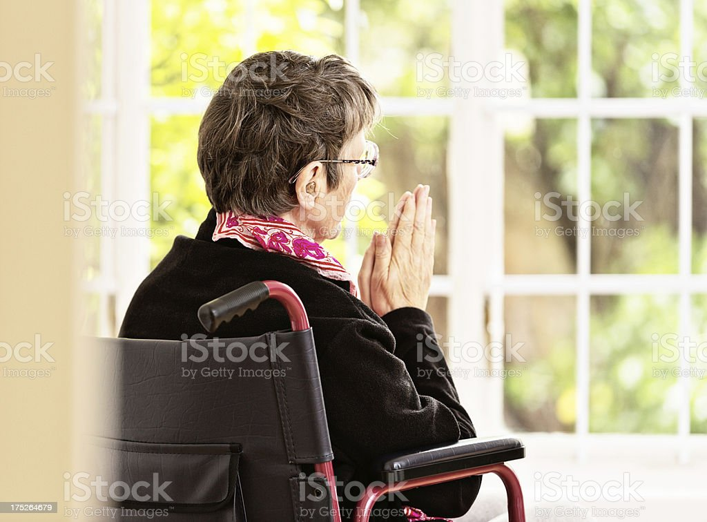 Elderly woman in wheelchair says her prayers royalty-free stock photo