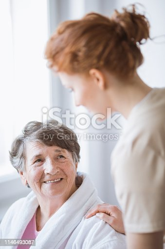 istock Elderly woman in white bathrobe and young volunteer at nursing home 1146493087