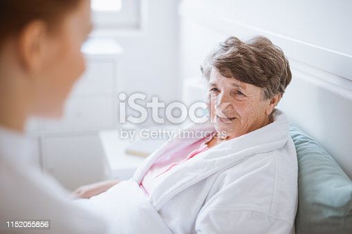 istock Elderly woman in white bathrobe and young volunteer at nursing home 1152055856