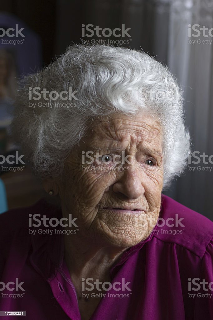 Elderly woman in window light stock photo
