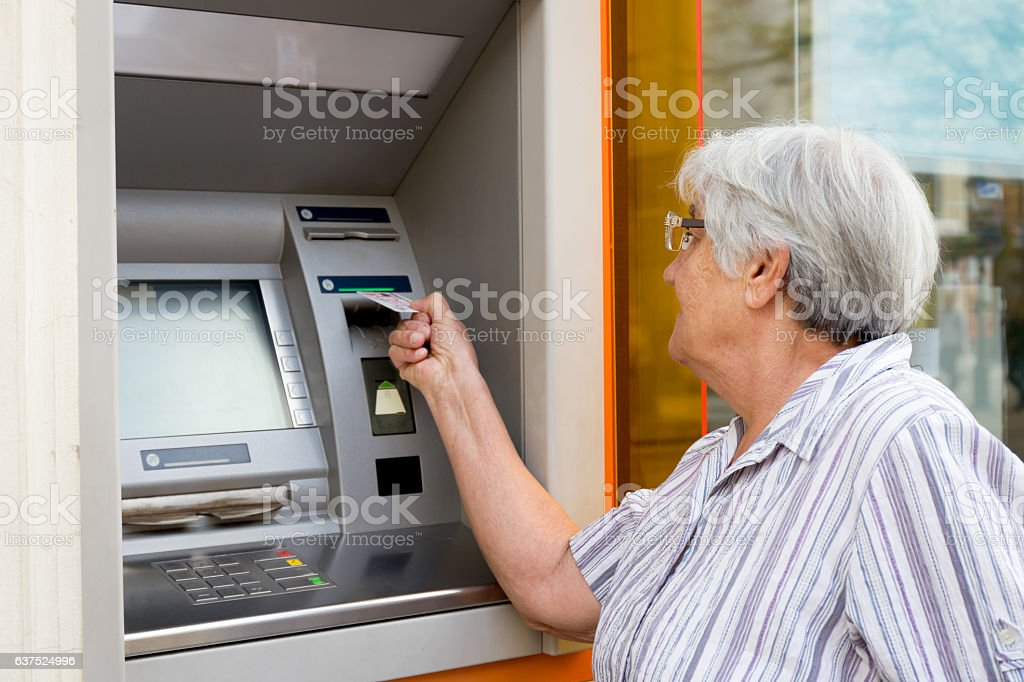 elderly woman inserting credit card to ATM stock photo