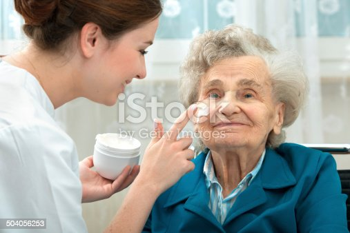 istock Elderly woman is assisted by nurse at home 504056253
