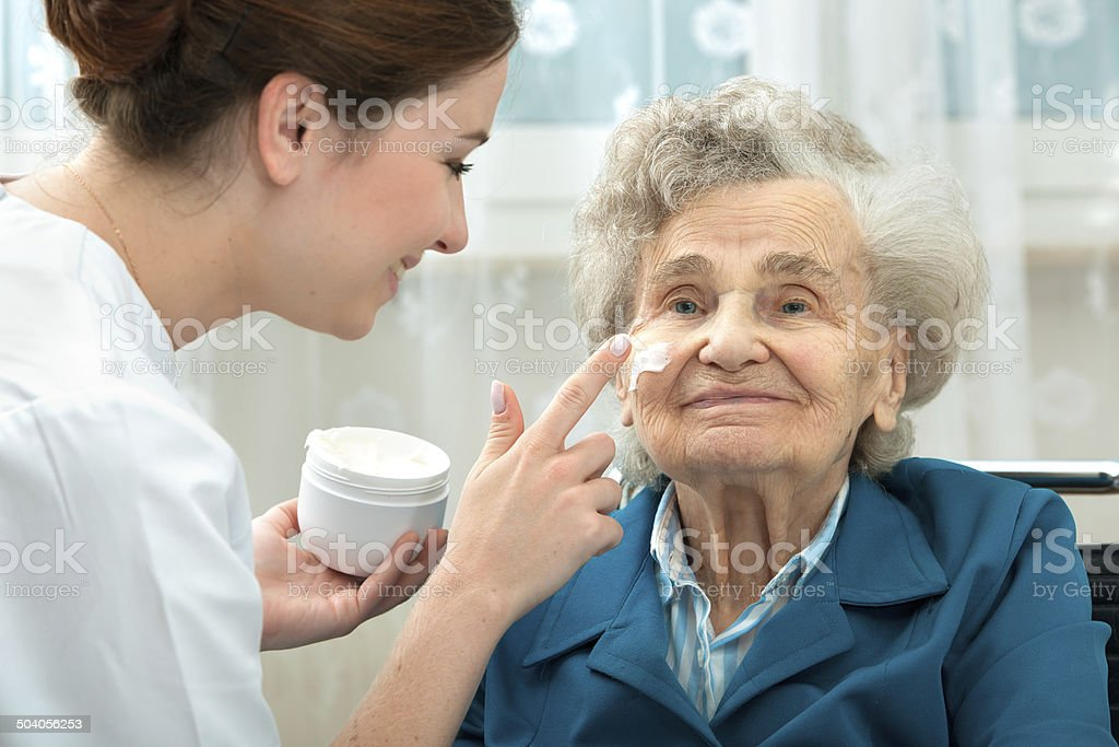 Elderly woman is assisted by nurse at home stock photo