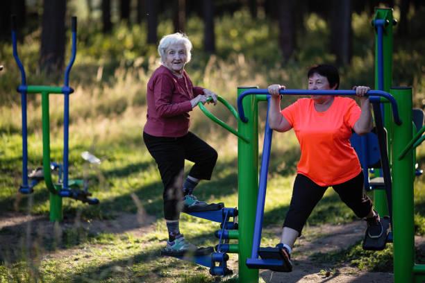 ältere frau tut übungen auf dem sport-spielplatz im park. - granny legs stock-fotos und bilder