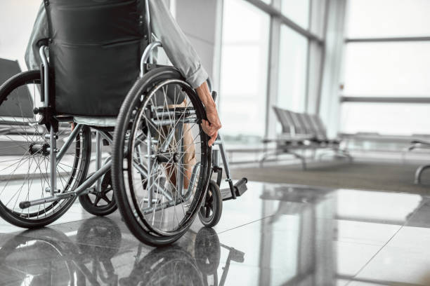 Elderly woman is using a wheelchair in front of the window stock photo