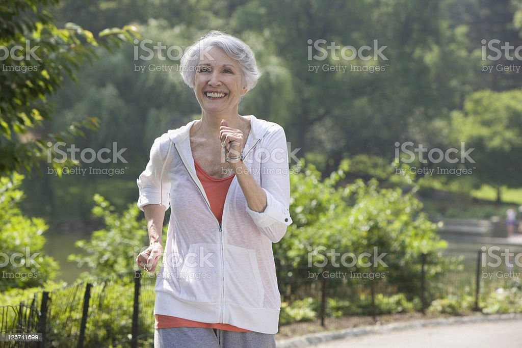 Elderly woman jogging in the park royalty-free stock photo