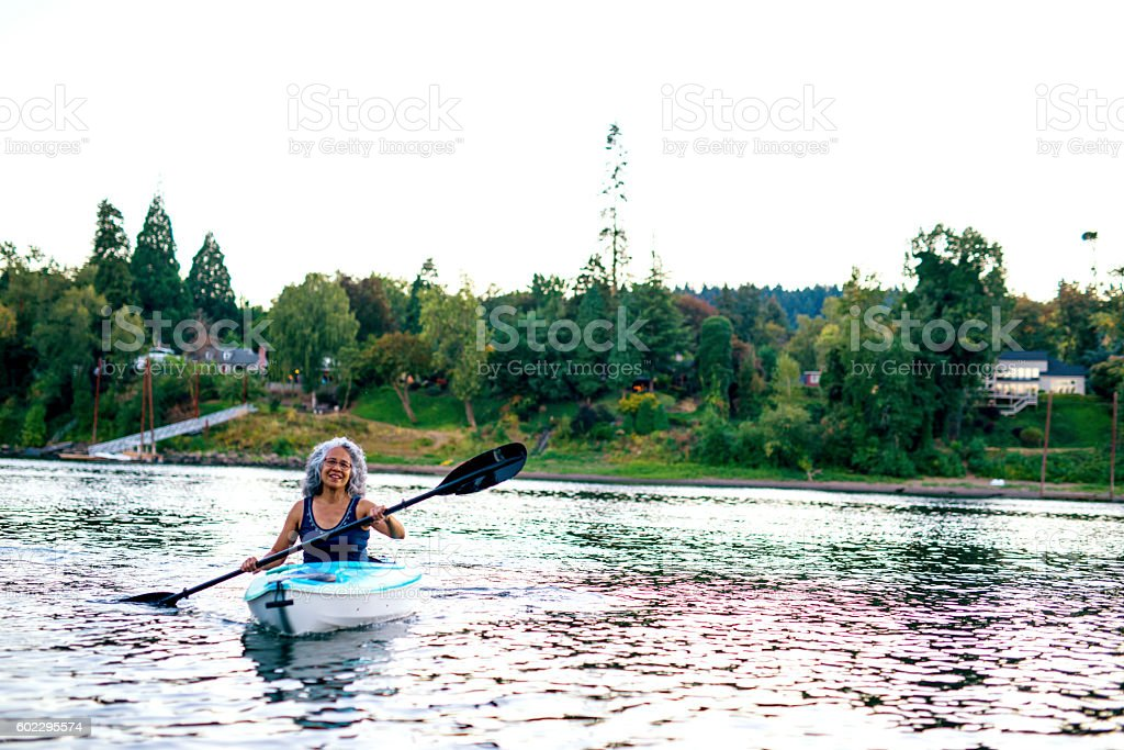 Elderly woman kayaing on the river stock photo