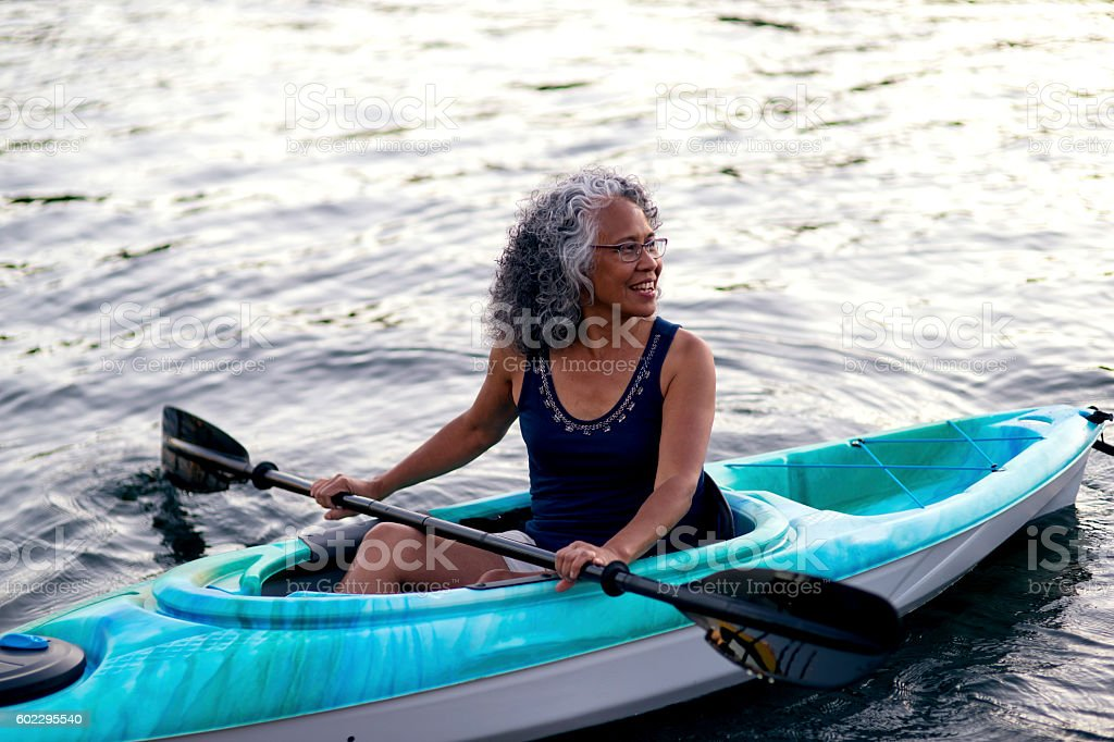 Elderly woman kayaking at sunset stock photo