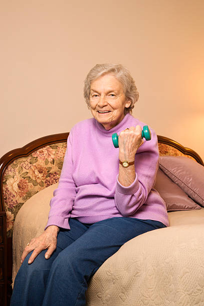 Elderly woman lifting weights. stock photo