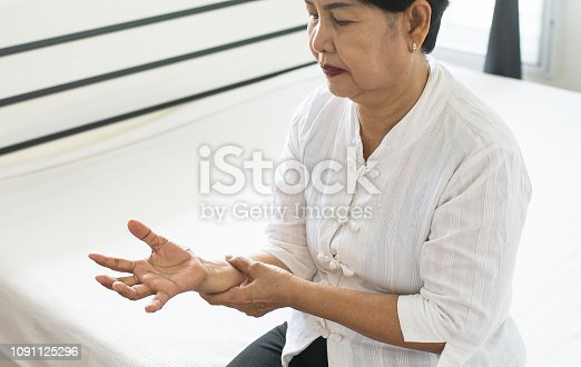 istock Elderly woman looking her hand and suffering with parkinson's disease symptoms 1091125296