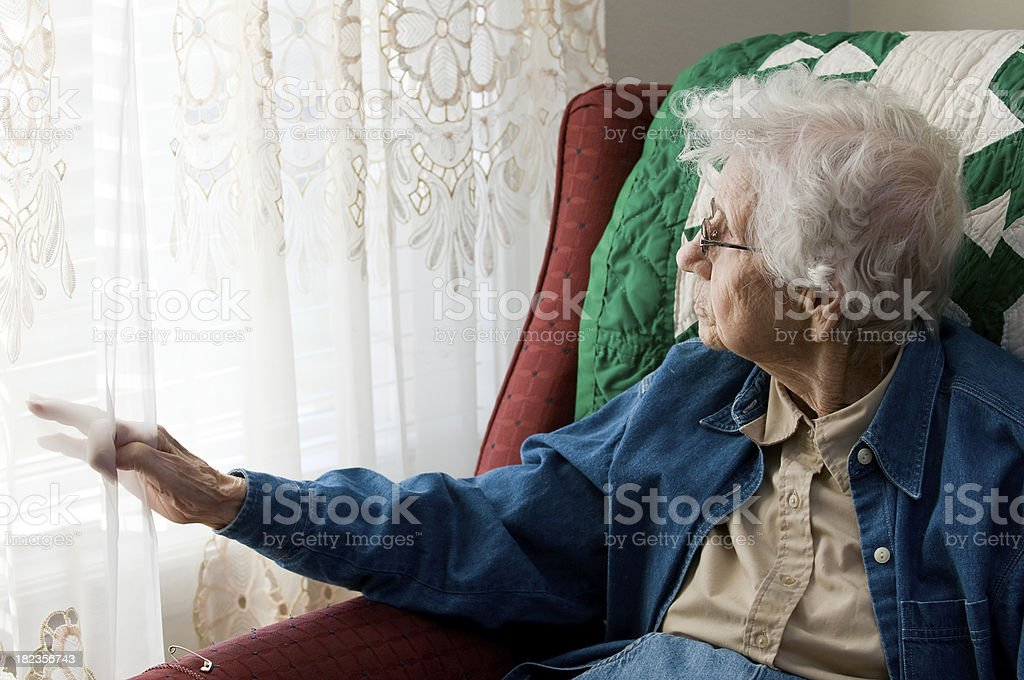 Elderly woman looking out window royalty-free stock photo