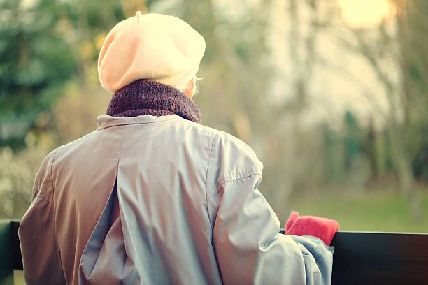 Elderly woman looks off into the distance. Rear view. stock photo