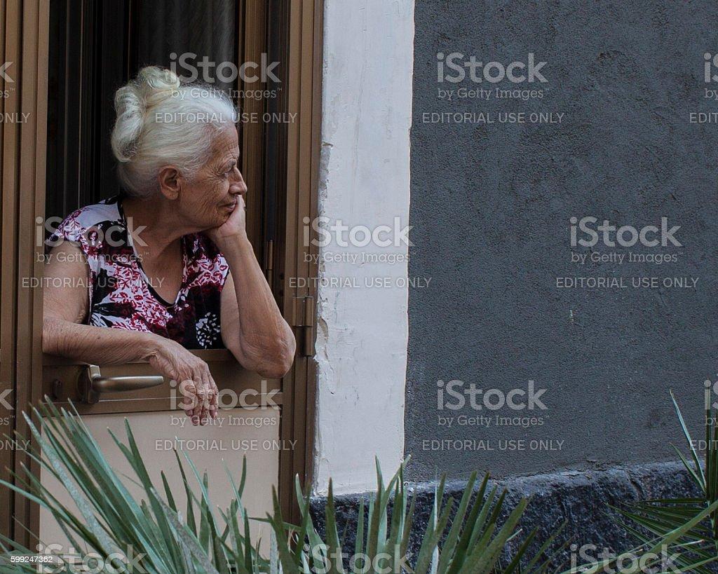 elderly woman looks people in the street stock photo