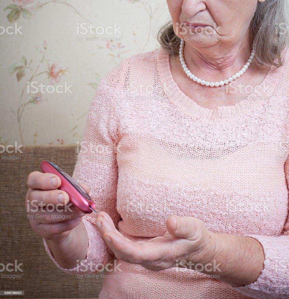 Elderly woman makes testing high blood sugar. royalty-free stock photo