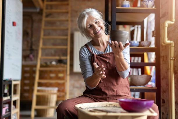 mulher idosa que faz o trabalho cerâmico com roda do oleiro - cerâmica artesanato - fotografias e filmes do acervo