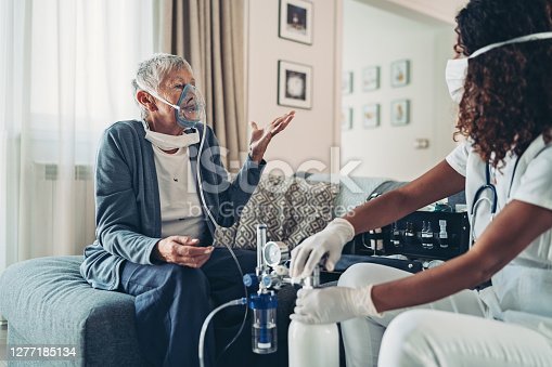 Doctor gives oxygen to an old woman