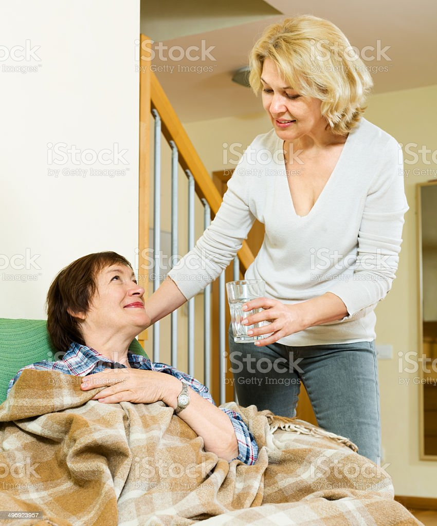 elderly woman offering medicine and water to pensioner stock photo